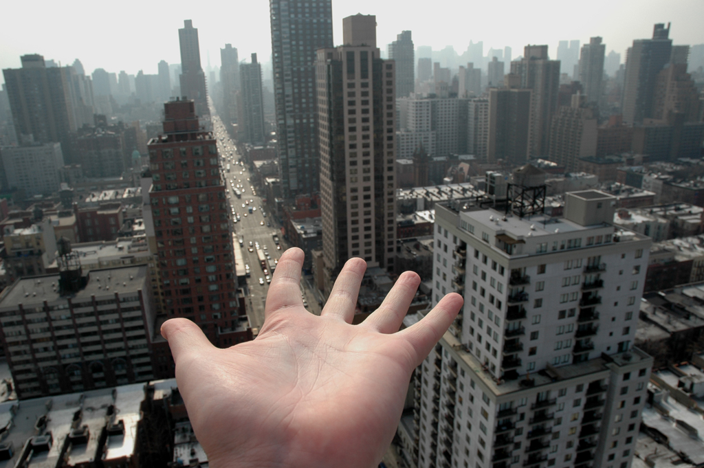 Hand reaching out to skyscrapers